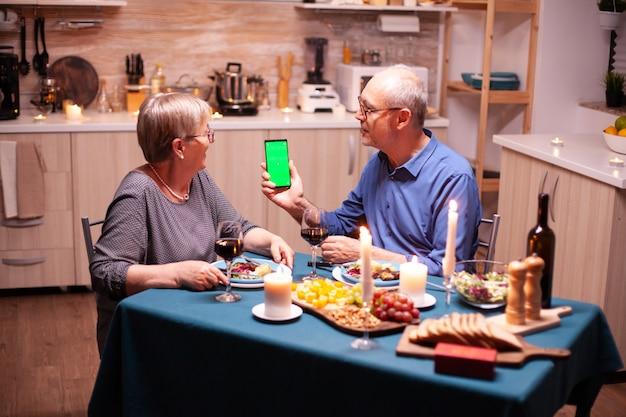 Vieux couple de retraités senior tenant un écran vert