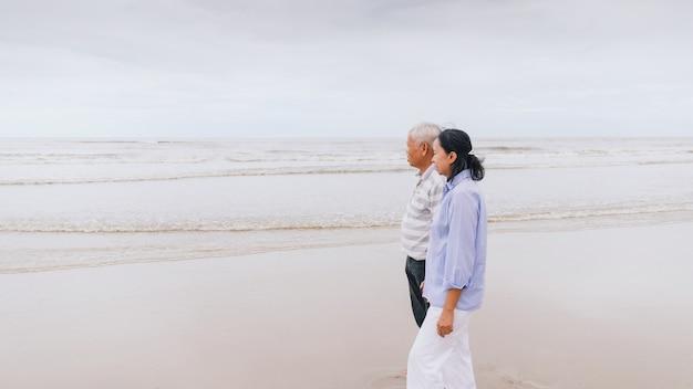 Vieux couples asiatiques marchant sur la plage au bord de la mer