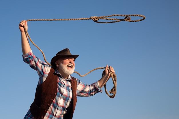 Vieux cowboy avec corde lasso au ranch ou rodéo. homme occidental barbu avec une veste marron et un chapeau attrapant un cheval ou une vache.