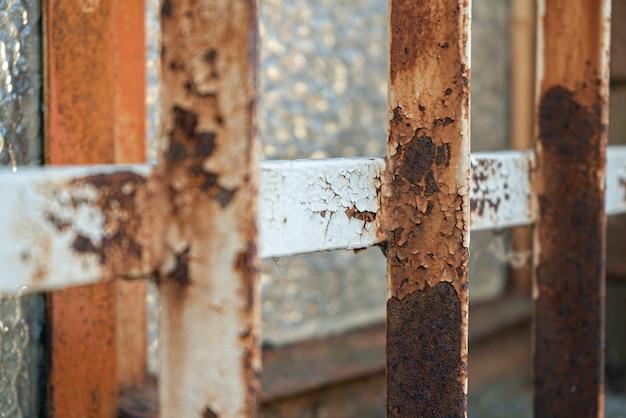 Vieux détail de grille rouillée dans une fenêtre de maison