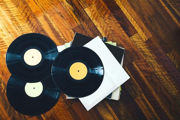 Vieux disque vinyle et une collection d'albums sur fond de bois