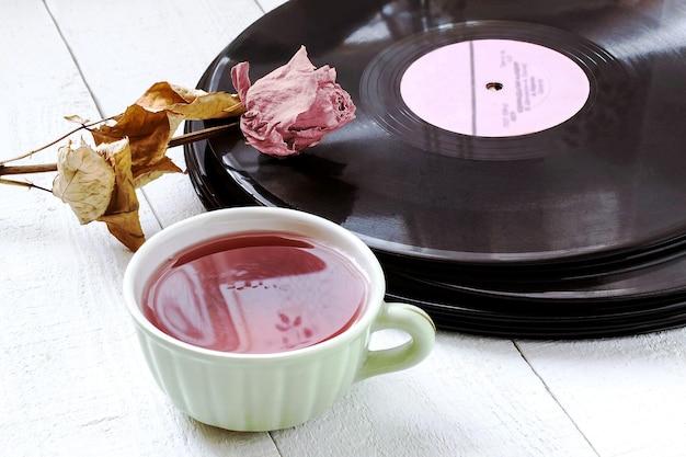 Vieux disques vinyles rose séchée et tasse de thé sur table en bois blanc