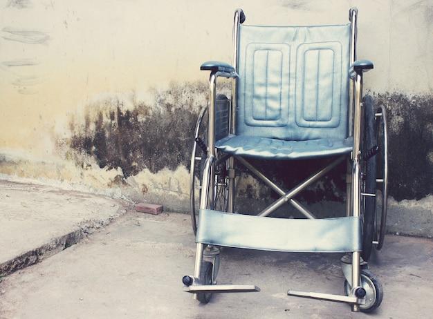 Vieux fauteuils roulants avec fond de mur