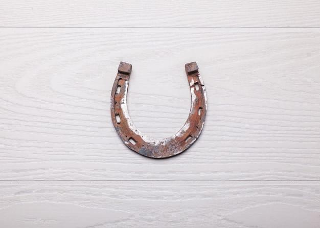 Vieux fer à cheval rouillé sur une surface blanche en bois
