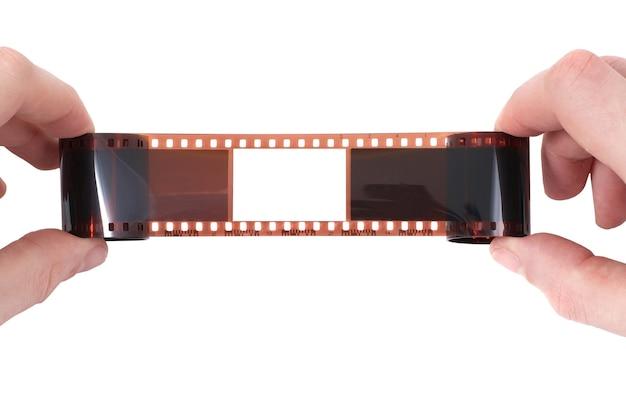 Vieux film avec cadre vide dans les mains sur une surface blanche