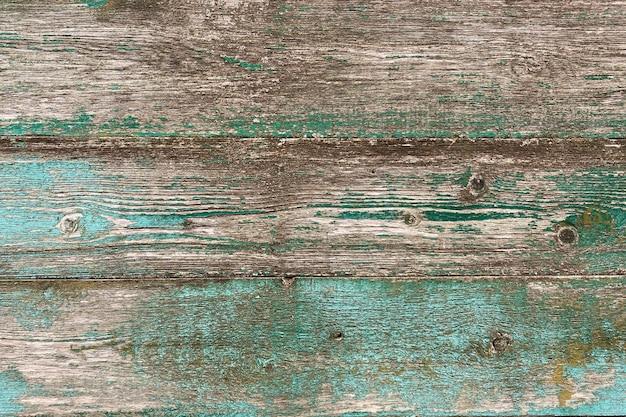 Vieux fond en bois brun-bleu avec peinture écaillée et mildiou vert. bois naturel de style grunge. vue de dessus. texture brute rabotée de pin conifère. surface de la table pour tirer à plat. espace de copie.