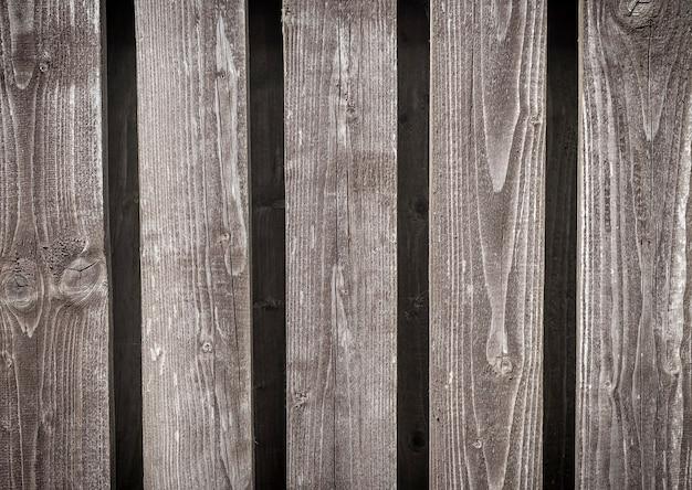 Vieux fond de clôture en bois gris naturel avec des planches verticales