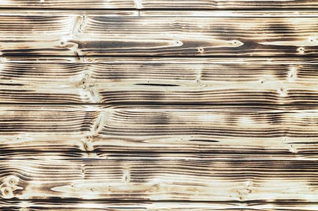 Vieux fond décoratif marron de planche de bois brûlé avec des planches horizontales. vue rapprochée à plat.