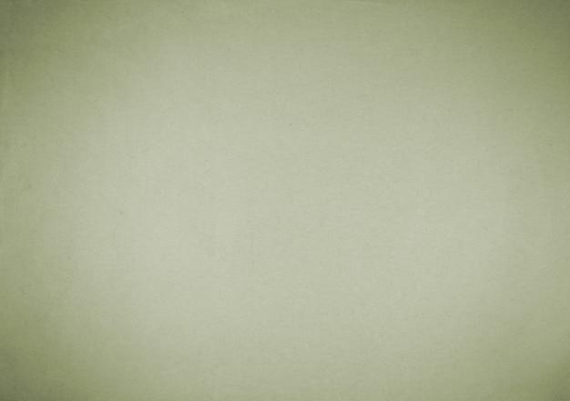 Vieux fond de papier vert avec vignette sombre.