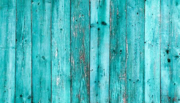 Vieux fond de texture bois bleu foncé. mur en bois peint. fond bleu une clôture lumineuse faite de planches verticales. la texture d'une planche de bois peut être utilisée pour l'arrière-plan. un peu de peinture craquelée.