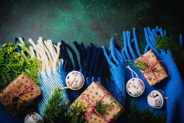 Vieux fond vert béton avec plaid chaud en haut, coffrets cadeaux et cloches. style vintage rustique. contexte du nouvel an. vue de dessus avec espace de copie.