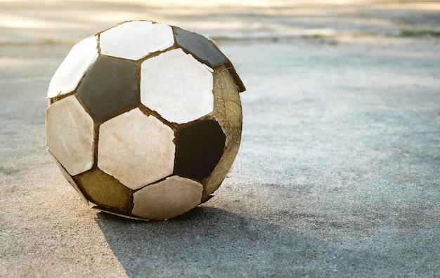 Vieux football sur le sol en béton.