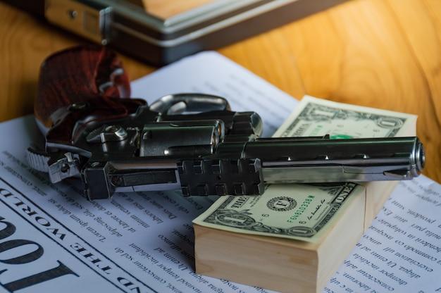 Les vieux fusils sont placés sur le dollar de la banque et les journaux, sur une table en bois.