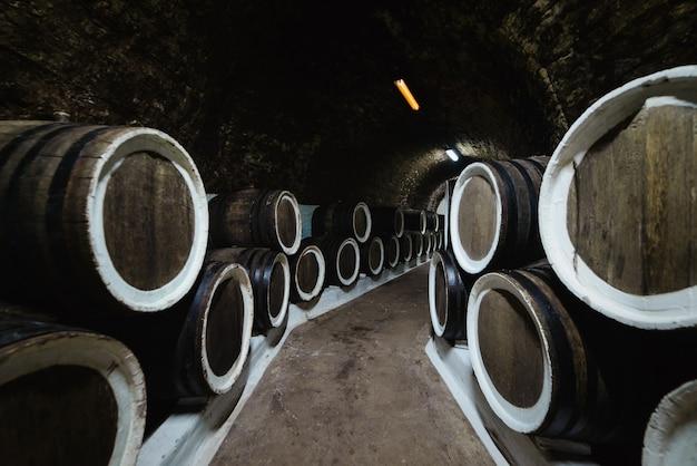 Vieux fûts de chêne à vin dans une cave à vin stockée dans une cave