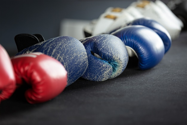 Le vieux gant de boxe en cuir sur le sol dans la salle de gym.