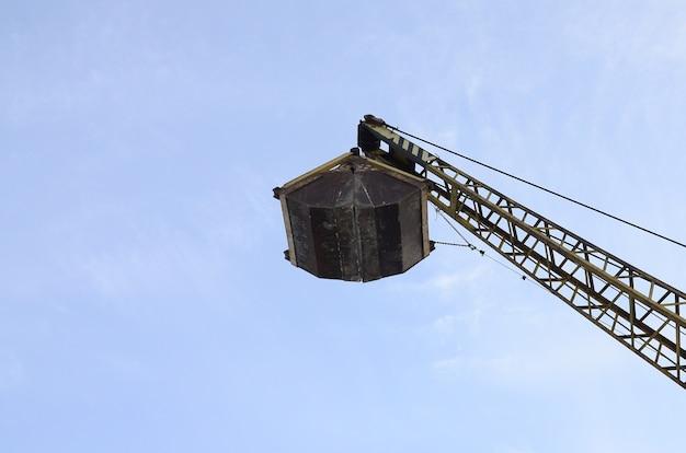 Vieux grappin mécanique jaune sur fond de ciel bleu