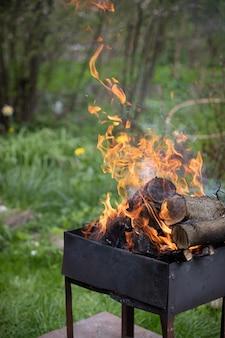 Vieux gril de barbecue avec des bûches de bois enflammées