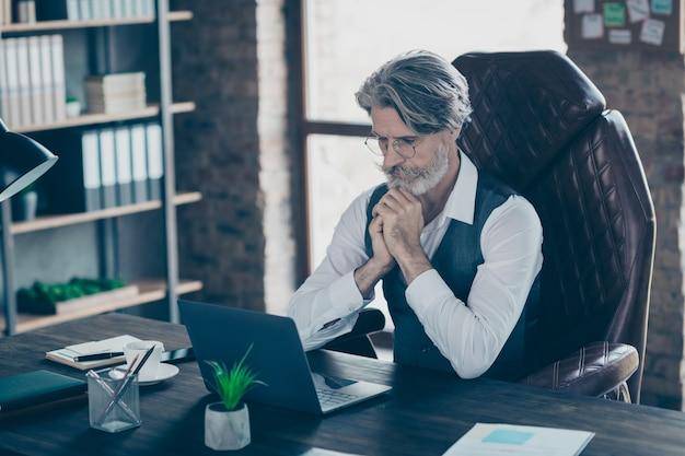 Vieux homme d'affaires axé sur le travail de table assis sur un ordinateur portable pense au bureau
