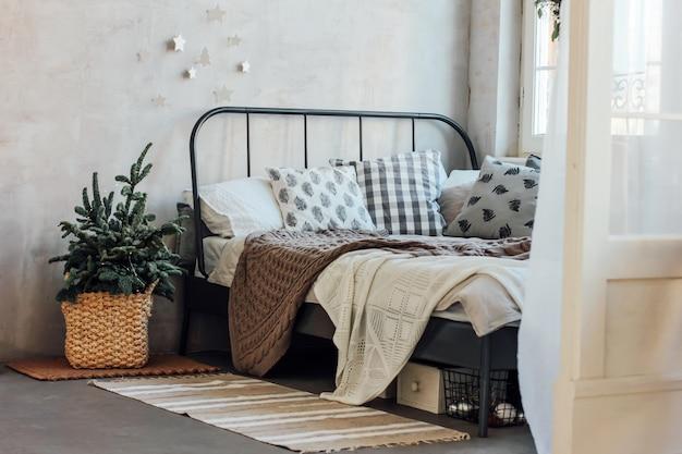 Le vieux lit avec des oreillers et une couverture tricotée. chris minimaliste