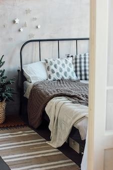 Le vieux lit avec des oreillers et une couverture tricotée. design de noël minimaliste