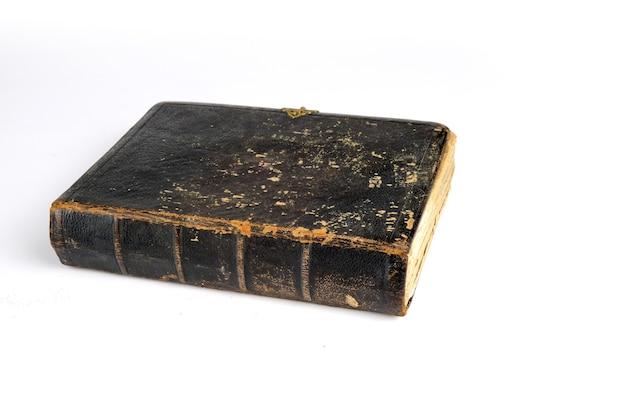 Un vieux livre ancien est allongé sur un tableau blanc isolé