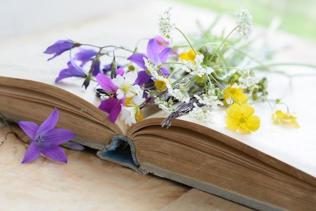 Vieux livre avec bouquet de fleurs de prairie, surface vintage nostalgique