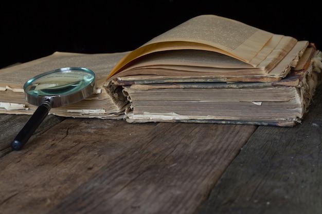 Un vieux livre brun et une loupe sur fond rustique.