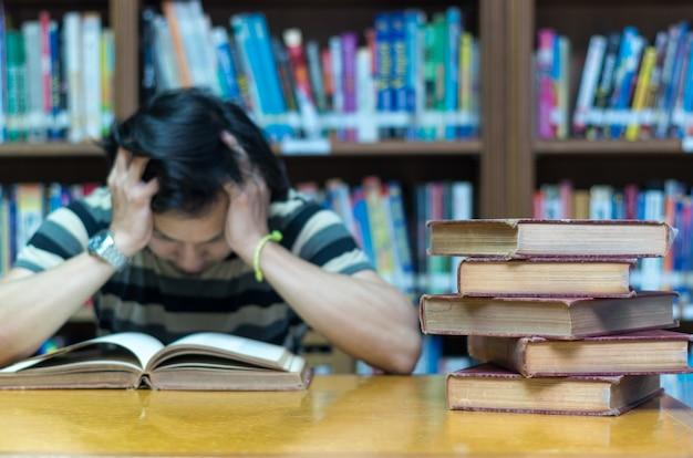 Vieux livre sur le bureau dans la bibliothèque avec l'homme lisant l'arrière-plan du livre