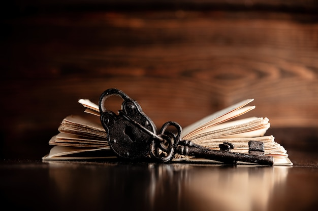 Vieux livre et clé sur table en bois