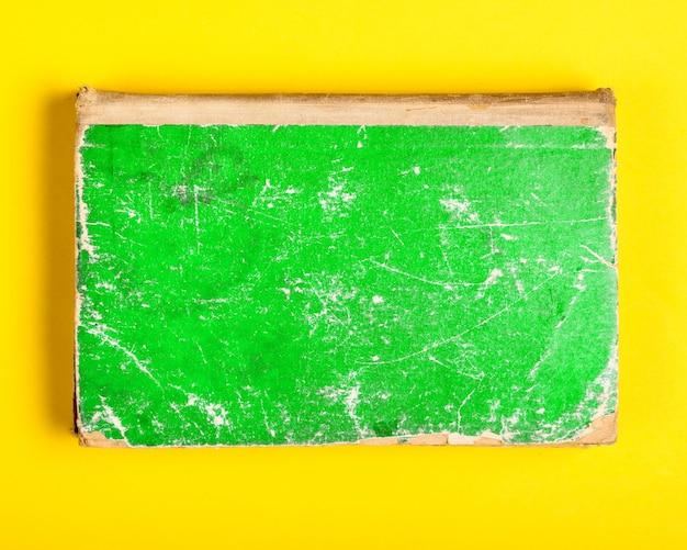 Vieux livre avec couverture minable verte sur fond jaune