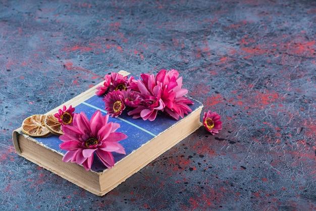 Un vieux livre avec du citron séché en tranches et des fleurs violettes.