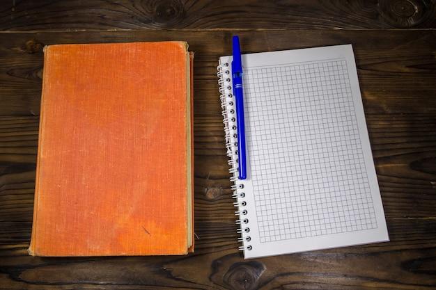 Vieux livre fermé, bloc-notes et stylo sur le bureau en bois