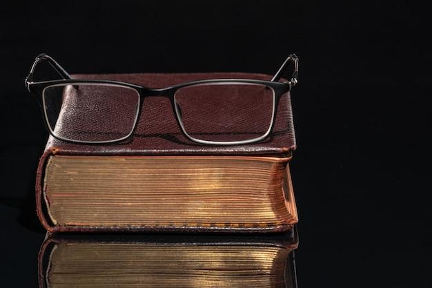 Un vieux livre avec des lunettes allongé dessus.