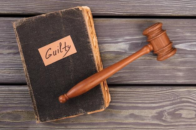 Vieux livre marteau et verdict de culpabilité. concept de justice de première instance. vue de dessus à plat.