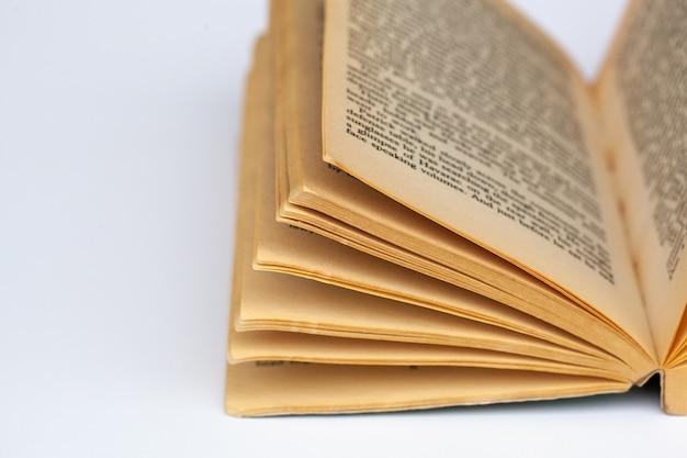 Vieux livre ouvert avec un ot de pages sur fond blanc