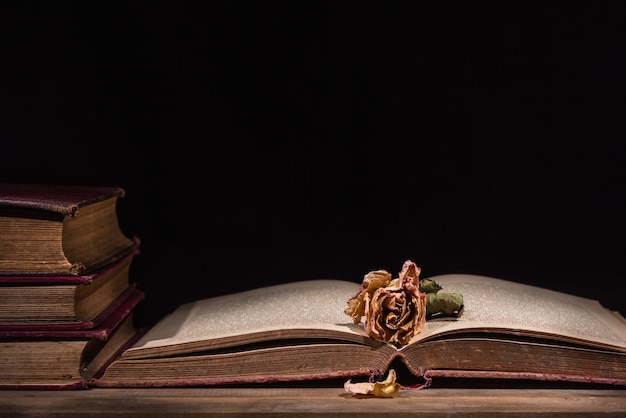 Vieux livre ouvert et pétales secs tombant sur une table en bois