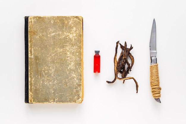 Un vieux livre, des racines et une ampoule de sang. attributs pour la magie, la divination et l'occultisme.