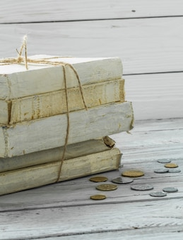 Vieux livres blancs avec de l'argent et des pièces sur un mur en bois