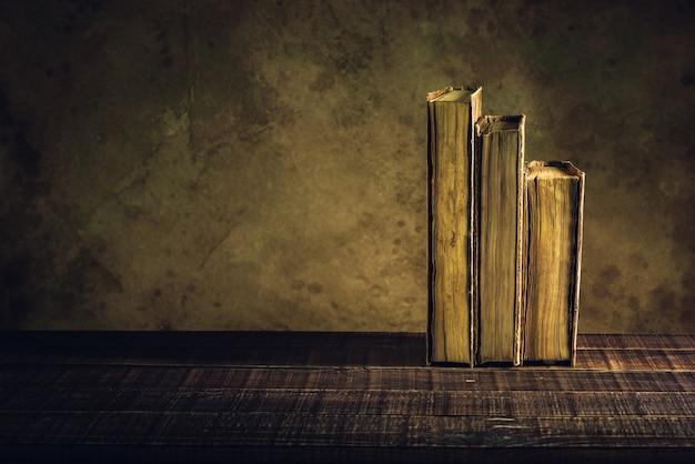 Vieux livres sur bois et fond de papier âgés