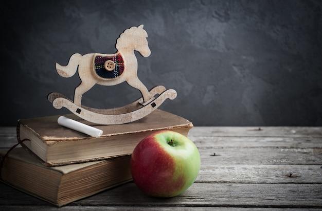 Vieux livres et cheval jouet en bois