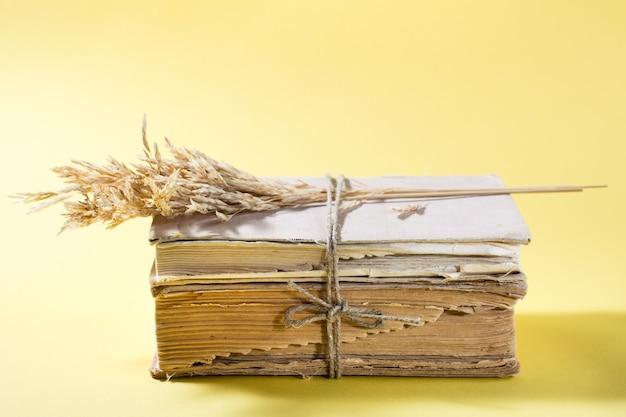 Vieux livres et épis de maïs secs attachés avec une corde dans une table jaune. bien-être, harmonie, inclusion. espace de copie
