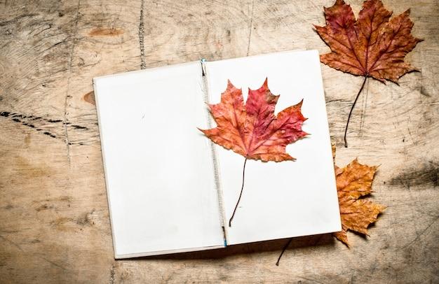 Vieux livres et feuilles d'automne. sur fond de bois.
