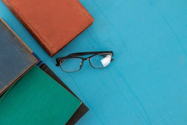 Vieux livres et lunettes noires sur un bois bleu-vert.