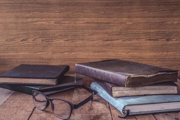 Vieux livres avec des lunettes sur la table en bois. espace libre pour le texte