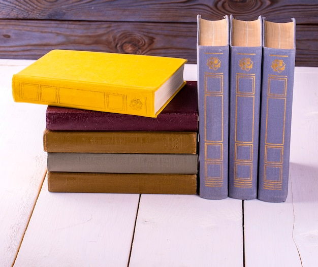 Vieux livres placés sur une table en bois blanche