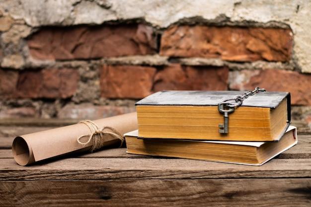 Vieux livres avec un rouleau et une clé sur une surface en bois rustique sur un fond de mur de briques.