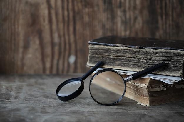 Vieux livres sur une table en bois et une loupe en verre