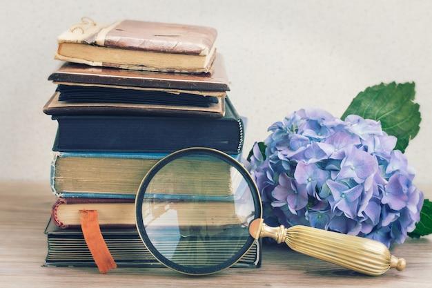 Vieux livres vintage avec des fleurs d'hortenzia bleues et un verre empilé sur une table