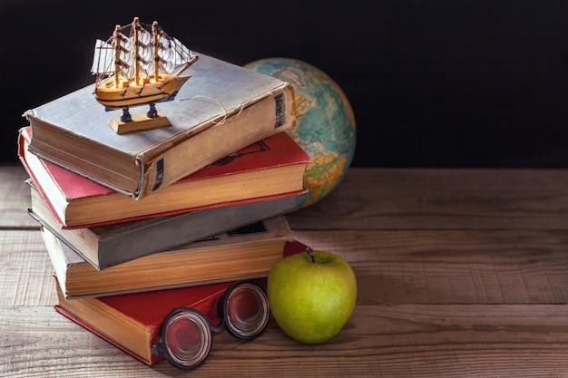 Les vieux manuels scolaires, manuels et fournitures scolaires sont posés sur une table en bois.