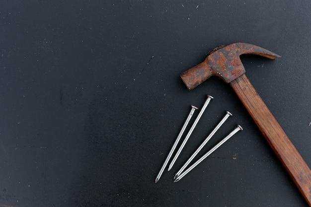 Vieux marteau et clou de fer sur bois noir
